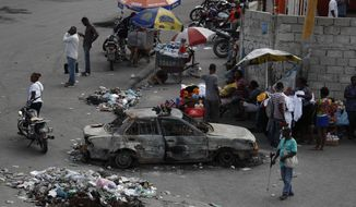 Vendors sell from sidewalk stands and people wait for public transport, alongside a car burned during Monday protests, in the Delmas district of Port-au-Prince, Haiti, Wednesday, Oct. 2, 2019. There was a relative pause in disturbances that have wracked Haiti's capital for weeks as protesters have tried to drive President Jovenel Moïse from power. (AP Photo/Rebecca Blackwell)