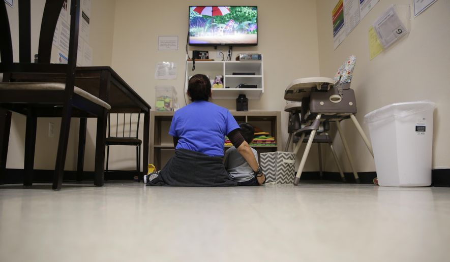 """A Comprehensive Health Services caregiver watches TV with a young migrant at a """"tender-age"""" facility for babies, children and teens, in Texas' Rio Grande Valley, Thursday, Aug. 29, 2019, in San Benito, Texas.  (AP Photo/Eric Gay) **FILE**"""