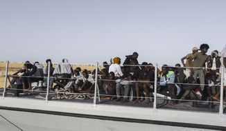 Rescued migrants sit ona coast guard boat in the city of Khoms, around 120 kilometers (75 miles) east of Tripoli, Libya, Tuesday, Oct. 1, 2019. (AP Photo/Hazem Ahmed)