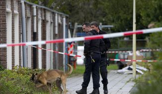 FILE - In this Wednesday, Sept. 18, 2019 file photo, forensic experts search for evidence in the area where a lawyer who represented a key witness in a major Dutch organized crime trial was gunned down in Amsterdam, in Amsterdam, Netherlands. Dutch police say they have arrested a man on suspicion of involvement in the shooting last month of a lawyer, a slaying that shocked the nation. Police said Thursday, Oct. 3 that the suspect was arrested on Tuesday in the investigation into the killing of lawyer Derk Wiersum in Amsterdam.(AP Photo/Peter Dejong, file)