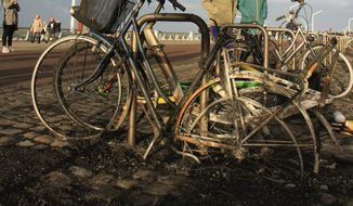 In this Jan. 1, 2019, image, burnt bicycles are seen on the beach in Scheveningen, near The Hague. A safety watchdog has published a scathing report into a giant New Year's Eve bonfire on a beach in The Hague that sent a blizzard of glowing embers onto nearby streets and buildings. The Dutch Safety Board report criticizes both the city's municipality for lax regulation and the builders of the giant stack of wooden pallets for breaching agreements about its size and the use of accelerants to help ignite the stack. (AP Photo/Mike Corder)