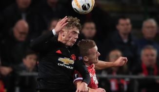Manchester United's Brandon Williams, left, and Alkmaar's Dani de Wit jump to head the ball during the group L Europa League soccer match between AZ Alkmaar and Manchester United at the ADO Den Haag stadium in The Hague, Netherlands, Thursday, Oct. 3, 2019. (AP Photo/Peter Dejong)