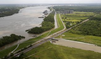 This May 1, 2019, photo, shows the Davis Pond Diversion, a project that diverts water from the Mississippi River, left, into the Barataria Basin to reduce coastal erosion in St. Charles Parish, La. Engineers hope to remake some eroded marshes by siphoning off sediment-rich water that can be channeled into coastal basins. (AP Photo/Gerald Herbert)