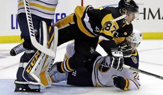Pittsburgh Penguins' Sidney Crosby (87) falls on top of Buffalo Sabres' Johan Larsson (22) during the second period of an NHL hockey game in Pittsburgh, Thursday, Oct. 3, 2019. (AP Photo/Gene J. Puskar)