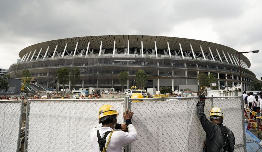 FILE - In this July 24, 2019, file, photo, workers adjust fences at the construction site of the New National Stadium, a venue for the opening and closing ceremonies at the Tokyo 2020 Olympics, in Tokyo. (AP Photo/Jae C. Hong, File)