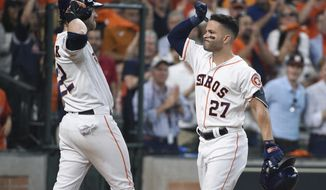 Houston Astros' Jose Altuve (27)  is congratulated by teammate Josh Reddick (22) after hitting a two-run home run against the Tampa Bay Rays in the fifth inning during Game 1 in baseball's American League Division Series in Houston, Friday, Oct. 4, 2019. (AP Photo/Michael Wyke)