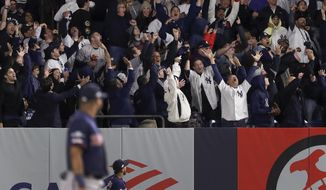 Baseball fans react after a solo home run by New York Yankees' Brett Gardner against the Minnesota Twins during the sixth inning of Game 1 of an American League Division Series baseball game, Friday, Oct. 4, 2019, in New York. (AP Photo/Frank Franklin II)