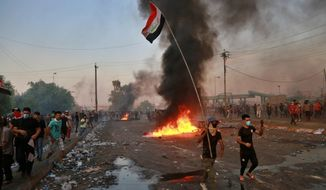 Anti-government protesters set fires and close a street during a demonstration in Baghdad, Iraq, Thursday, Oct. 3, 2019. Iraqi security forces fired live bullets into the air and used tear gas against a few hundred protesters in central Baghdad on Thursday, hours after a curfew was announced in the Iraqi capital on the heels of two days of deadly violence that gripped the country amid anti-government protests that killed over 19 people in two days. (AP Photo/Hadi Mizban)
