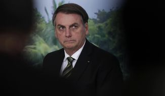 Brazil's President Jair Bolsonaro attends a ceremony to launch the Agro Nordeste program at the Palanalto presidential palace in Brasilia, Brazil, Oct. 1, 2019. According to officials, the program aims to boost sustainable economic and social development for small scale farmers in the rural northeast of Brazil. (AP Photo/Eraldo Peres)