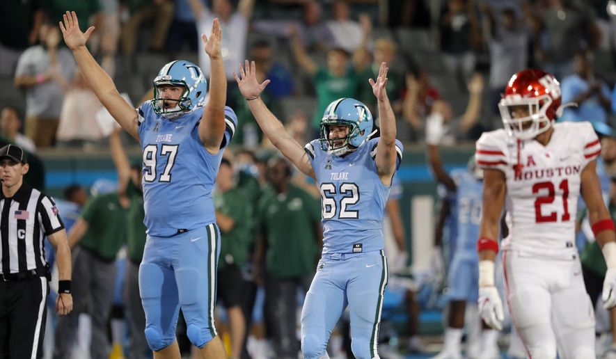 Tulane's Merek Glover (62) celebrates a go-ahead field goal with holder Ryan Wright (97) in front of Houston' Gleson Sprewell (21) during the second half of an NCAA college football game in New Orleans, Thursday, Sept. 19, 2019. Tulane won 38-31. (AP Photo/Gerald Herbert)