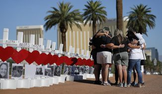 In this Oct. 1, 2019, file photo, people pray at a makeshift memorial for shooting victims in Las Vegas, on the anniversary of the mass shooting two years earlier. Two years after a shooter rained gunfire on country music fans from a high-rise Las Vegas hotel, MGM Resorts International reached a settlement that could pay up to $800 million to families of the 58 people who died and hundreds of others who were injured, attorneys announced Thursday, Oct. 3, 2019. (AP Photo/John Locher, File)