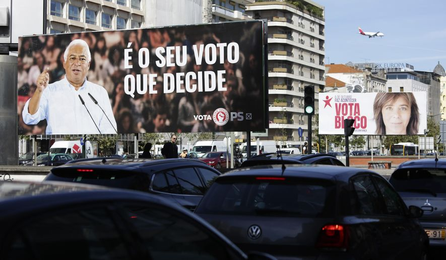 """Cars drive past billboards of Portuguese Prime Minister and Socialist Party leader Antonio Costa, left, and Left Bloc leader Catarina Martins, in Lisbon, Thursday, Oct. 3, 2019. Portugal will hold a general election on Oct. 6 in which voters will choose members of the next Portuguese parliament. Slogan on the Socialist's billboard reads in Portuguese, """"It's your vote that decides"""". (AP Photo/Armando Franca)"""