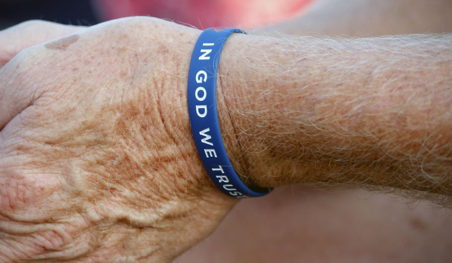 "A worshipper wears an ""In God We Trust"" wristband before evangelist The Rev. Franklin Graham speaks at the Decision America event at the Pitt County Fairgrounds in Greenville, N.C. on Wednesday, Oct. 2, 2019. (AP Photo/Chris Seward) ** FILE **"