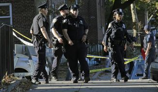 FILE - In this Sunday, Sept. 29, 2019 file photo, emergency personnel walk near the scene of a fatal shooting of a New York City police officer in the Bronx borough of New York. A funeral is scheduled to begin Friday morning, Oct. 4, for a New York City police officer killed by friendly fire during a struggle with an armed man. Authorities say Officer Brian Mulkeen was fatally hit Sunday by two police bullets while struggling with an armed man in the Bronx. (AP Photo/Seth Wenig, File)