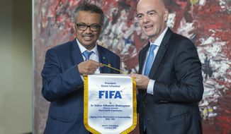 """FIFA President Gianni Infantino, right, and Tedros Adhanom Ghebreyesus, left, Director General of the World Health Organization (WHO), pose for the media at the World Health Organization (WHO) headquarters in Geneva, Switzerland, Friday, Oct. 4, 2019. FIFA president Gianni Infantino says a new partnership with the U.N. health agency is a """"starting point"""" to help leverage the global appeal of soccer to improve health outcomes. Infantino says the association with the World Health Organization will work to """"elaborate concrete solutions"""" and insists that FIFA's corporate sponsors, including Coca-Cola and McDonald's, are """"progressing"""" on health. (Martial Trezzini/Keystone via AP)"""