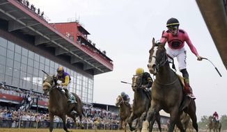 FILE - In this May 18, 2019, file photo, jockey Tyler Gaffalione, right, reacts aboard War of Will, as they crosses the finish line first to win the Preakness Stakes horse race at Pimlico Race Course in Baltimore. The owners of the historic racetrack that hosts the Preakness Stakes and Baltimore officials have reached an agreement to keep the Triple Crown series' middle jewel in the city. (AP Photo/Steve Helber, File) ***FILE**