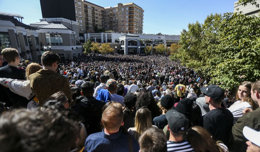 "Thousands pack into The Gateway in Salt Lake City for Kanye West's ""Sunday Service,"" Saturday, Oct. 5, 2019. People were standing on and climbing up anything they could find to catch a glimpse of West. (Colter Peterson/The Deseret News via AP)"