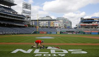 A groundskeeper paints a logo on the field at Nationals Park in Washington, Saturday, Oct. 5, 2019. Game 3 of the National League Division Series between the Los Angeles Dodgers and the Washington Nationals is scheduled to take place Sunday. (AP Photo/Patrick Semansky) ** FILE **