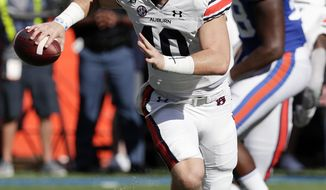 Auburn quarterback Bo Nix, left, looks for a receiver as he is rushed by Florida defensive lineman Luke Ancrum (98) during the first half of an NCAA college football game, Saturday, Oct. 5, 2019, in Gainesville, Fla. (AP Photo/John Raoux)