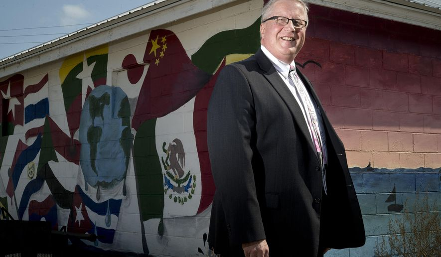 In this Tuesday, Sept. 10, 2019 photo, Mark Prosser, Storm Lake Public Safety Director and Chief of Police, stands at a building decorated with murals of flags representing the countries of the city's immigrants. in Storm Lake, Iowa. Prosser is a member of the Law Enforcement Immigration Task Force and an outspoken proponent of immigrants in Storm Lake and beyond. (Tim Hynds/Sioux City Journal via AP)