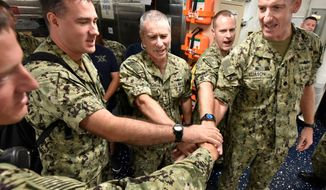 """In a Friday, September 27, 2019 photo, Cdr. Pat Eliason, right, Commanding Officer of the USS The Sullivans and Rear Admiral Roy Kitchener, center, join crew members in cheering the ship's motto, """"We Stick Together"""" during a reunion of family members and former crew members at Mayport Naval Station, Florida. The ship is a guided missile destroyer named for five Sullivan brothers who died when their ship, the USS Juneau was sunk by a Japanese submarine in World War II. (Will Dickey/The Florida Times-Union via AP)"""