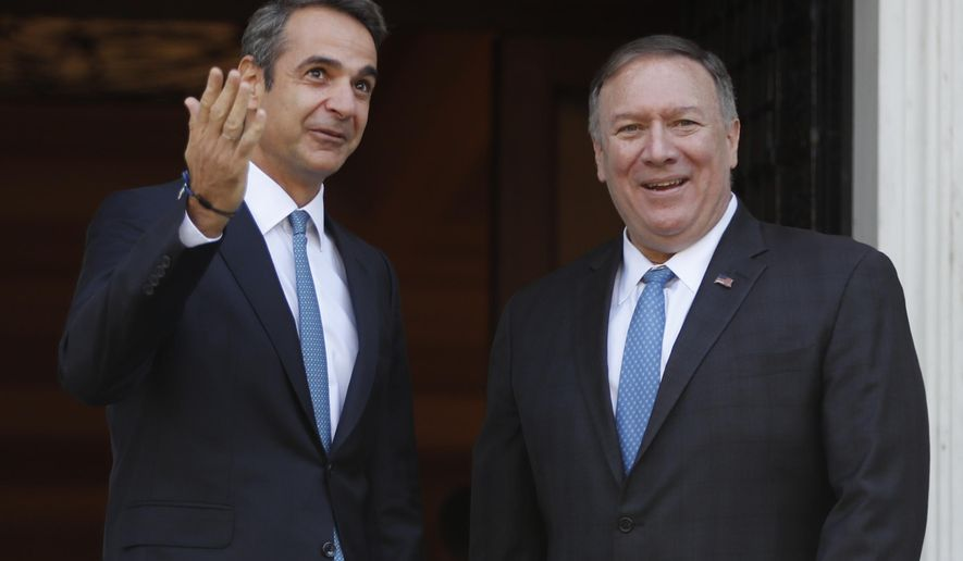 Greece's Prime Minister Kyriakos Mitsotakis left, gestures as he welcomes U.S. Secretary of State Mike Pompeo, right, prior to their meeting at Maximos Mansion in Athens, Saturday, Oct. 5, 2019. Pompeo is visiting southeastern European countries to show support for new NATO members in the region. (AP Photo/Thanassis Stavrakis)