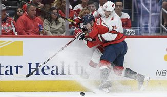 Washington Capitals defenseman Dmitry Orlov (9), of Russia, battles for the puck against Carolina Hurricanes center Sebastian Aho (20), of Finland, during the first period of an NHL hockey game, Saturday, Oct. 5, 2019, in Washington. (AP Photo/Nick Wass)