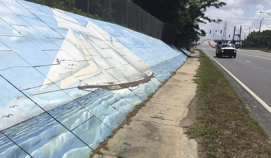 FILE - In this May 30, 2019, file photo, traffic passes a mural of the slave ship Clotilda along Africatown Blvd. in Mobile, Ala. The discovery of the last ship that brought Africans to the United States as slaves may offer a test case for reparations. Relatives of steamship owner Timothy Meaher, who financed the trip in 1860, still live in Mobile, Alabama. So do descendants of the people he enslaved. Many Clotilda descendants say reconciliation with the Meahers would suffice. Others say they want more. The discussion comes as Congress considers whether to create a reparations study commission.(AP Photo/Kevin McGill, File)