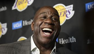FILE - In this April 9, 2019, file photo, Magic Johnson speaks to reporters prior to an NBA basketball game between the Los Angeles Lakers and the Portland Trail Blazer in Los Angeles. Johnson might actually miss the Lakers if he was not always checking up on them. Johnson quit as the team's president of basketball operations at the end of the last season, leaving him out of a gym, but not out of the loop, as Los Angeles opened training camp. (AP Photo/Mark J. Terrill, File)