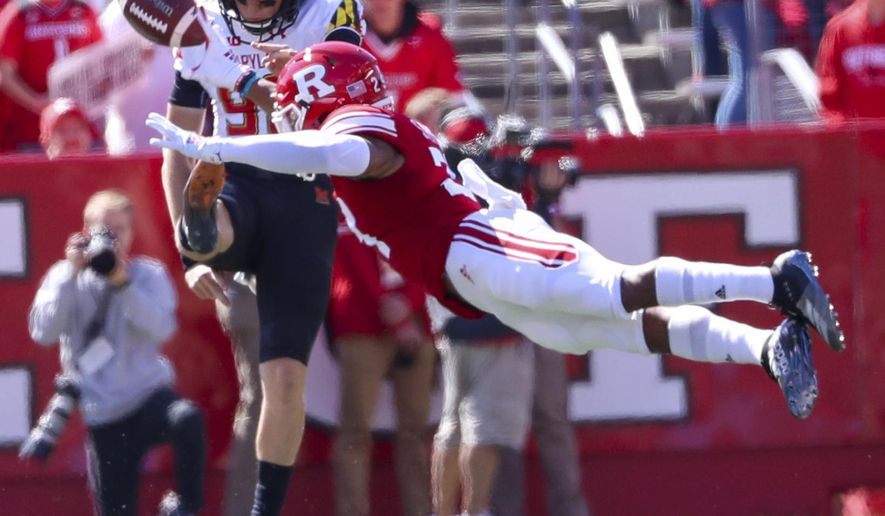 Maryland punter Anthony Pecorella (98) has this kick partially blocked by Rutgers defensive back Lawrence Stevens (29) during the first half  of an NCAA college football game, Saturday Oct. 5, 2019, in Piscataway, N.J. (Andrew Mills/NJ Advance Media via AP)