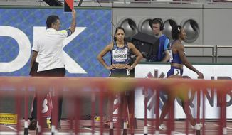 Brianna Mcneal, of the United States, right, walks away after being disqualified for a false start in a the women's 100 meter hurdles heat at the World Athletics Championships in Doha, Qatar, Saturday, Oct. 5, 2019. (AP Photo/Petr David Josek)