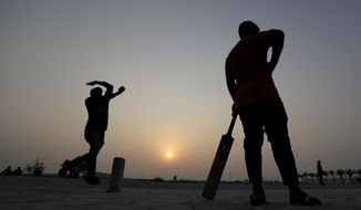 A man comes in to bowl during a cricket match on a patch of wasteland in Doha, Qatar, Friday, Oct. 4, 2019. At dozens of makeshift pitches on wasteland around Doha, workers from all over South Asia gather to play on their one free day of the week. The stadium hosting the world track and field championship, and the arenas for the 2022 soccer World Cup, are at best distant lights on the horizon. (AP Photo/Petr David Josek)