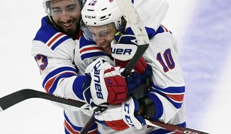 New York Rangers center Mika Zibanejad (93) celebrates his team's win with teammate Artemi Panarin (10) after an NHL hockey game, Saturday, Oct. 5, 2019 in Ottawa, Ontario. (Justin Tang/The Canadian Press via AP)