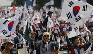 """Protesters shout slogans as they wave national flags and signs during a rally denouncing South Korea's Justice Minister Cho Kuk in Seoul, South Korea, Saturday, Oct. 5, 2019. The letters read """"Arrest Cho Kuk"""" and """"Moon Jae-in, resign."""" (AP Photo/Lee Jin-man)"""