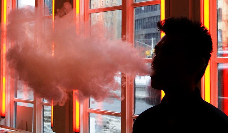 In this Feb. 20, 2014, file photo, a patron exhales vapor from an e-cigarette at a store in New York. (AP Photo/Frank Franklin II, File)