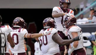 Virginia tight end Dalton Keene, right, celebrates with wide receiver Damon Hazelton, top right, and other teammates after scoring a touchdown during the first half of an NCAA college football game against Miami, Saturday, Oct. 5, 2019, in Miami Gardens, Fla. (AP Photo/Lynne Sladky)