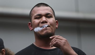 """In this June 3, 2018 photo, Tusitala """"Tiny"""" Toese a member of Proud Boys and Patriot Prayer smokes as dueling demonstrations erupted in downtown Portland, Ore., between Rose City Antifa and Patriot Prayer. Toese who rose to prominence for fighting in Portland during political protests and fled the Pacific Northwest after being indicted on felony assault charges has been arrested on Friday, Oct. 5, 2019. (Mark Graves/The Oregonian via AP)"""
