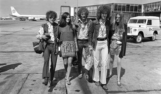 Members of the blue-based rock group Cream depart from Heathrow Airport for their American tour, London, England, Aug. 20, 1967.  The trio, walking with unidentified female companions, from left are, base guitarist Jack Bruce, drummer Ginger Baker, and lead guitarist Eric Clapton.  (AP Photo/Peter Kemp)