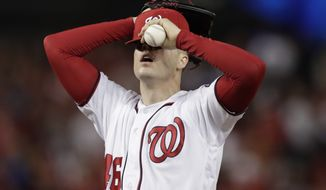 Washington Nationals starting pitcher Patrick Corbin covers his face after allowing a two-run double to Los Angeles Dodgers Russell Martin during the sixth inning in Game 3 of a baseball National League Division Series on Sunday, Oct. 6, 2019, in Washington. (AP Photo/Julio Cortez)