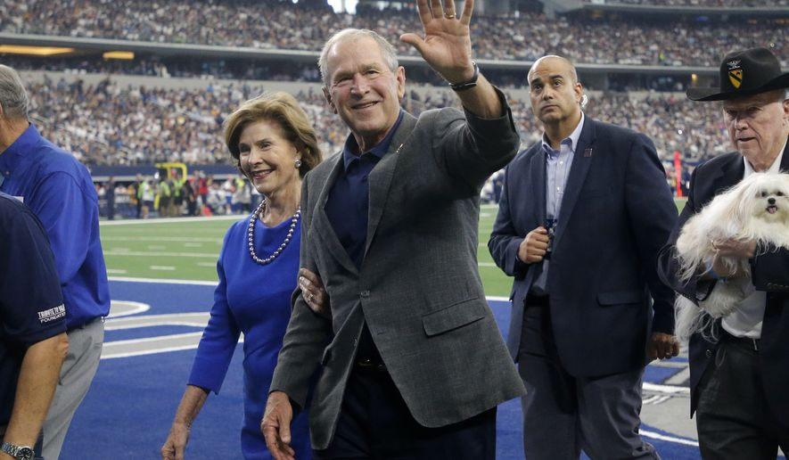 Former President George W. Bush and wife Laura walk off the field after participating in a ceremony with Medal of Honor recipients in the first half of an NFL football game between the Green Bay Packers and Dallas Cowboys in Arlington, Texas, Sunday, Oct. 6, 2019. (AP Photo/Michael Ainsworth)