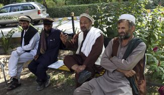 In this Tuesday, Oct. 1, 2019, photo, Aziz Rahman, second, right, a village elder, who had contracted the farmers to harvest the pine nuts, speaks during an interview to the Associated Press in Jalalabad city east of Kabul, Afghanistan,  Anger is mounting over the increasing numbers of civilians dying in misdirected US aerial strikes and heavy- handed tactics of CIA-trained Afghan force. Some Afghans calling for Americans to be tried in Afghan courts (AP Photo/Rahmat Gul)