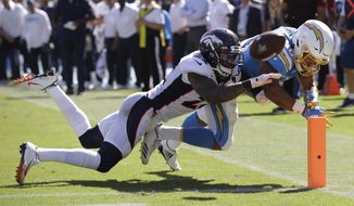 Denver Broncos defensive back Kareem Jackson, left, forces a fumble by Los Angeles Chargers running back Austin Ekeler at the goal line during the first half of an NFL football game Sunday, Oct. 6, 2019, in Carson, Calif. (AP Photo/Marcio Jose Sanchez)
