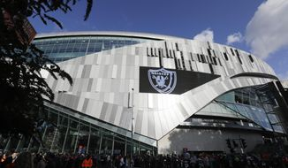 Fans wait to enter Wembley stadium before an NFL football game between the Chicago Bears and the Oakland Raiders, Sunday, Oct. 6, 2019, in London. (AP Photo/Kirsty Wigglesworth)
