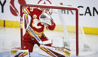 Calgary Flames goalie David Rittich ducks as the puck deflects off his mask during the third period of an NHL hockey game against the Vancouver Canucks on Saturday, Oct. 5, 2019, in Calgary, Alberta. (Jeff McIntosh/The Canadian Press via AP)