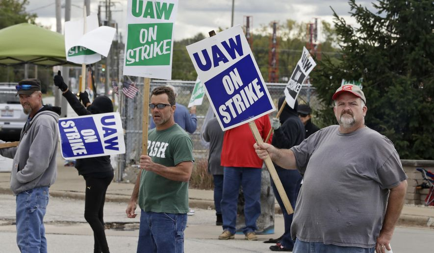 John Kirk, right, a 20-year-employee, pickets with co-workers outside the General Motors Fabrication Division, Friday, Oct. 4, 2019, in Parma, Ohio. (AP Photo/Tony Dejak)