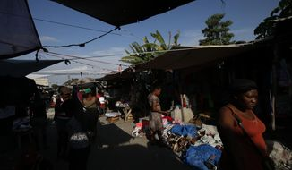 Shoppers browse in a market in Leogane, Haiti, Saturday, Oct. 5, 2019. The political turmoil is hitting cities and towns outside the capital of Port-au-Prince especially hard, forcing non-government organizations to suspend aid as barricades ranging from large rocks to burning tires cut off the flow of goods between the city and the countryside, further deepening poverty in places like Leogane.(AP Photo/Rebecca Blackwell)