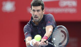 Novak Djokovic of Serbia returns a shot against John Millman of Australia during a final of Japan Open tennis championships in Tokyo, Sunday, Oct. 6, 2019. (AP Photo/Koji Sasahara)