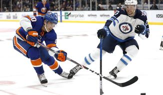New York Islanders center Derick Brassard (10) and Winnipeg Jets defenseman Carl Dahlstrom (23) reach for the puck during the second period of an NHL hockey game Sunday, Oct. 6, 2019, in Uniondale, N.Y. (AP Photo/Michael Owens)