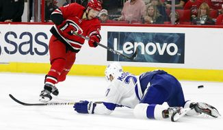 Tampa Bay Lightning's Ryan McDonagh (27) goes to the ice to attempt to block a shot by Carolina Hurricanes' Warren Foegele (13) during the second period of an NHL hockey game, in Raleigh, N.C., Sunday, Oct. 6, 2019. (AP Photo/Karl B DeBlaker)