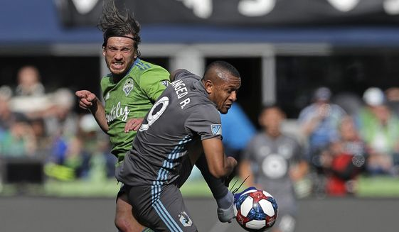 Seattle Sounders midfielder Gustav Svensson, left, battles for loose ball with Minnesota United forward Angelo Rodriguez, right, during the second half of an MLS soccer match, Sunday, Oct. 6, 2019, in Seattle. The Sounders won 1-0. (AP Photo/Ted S. Warren)